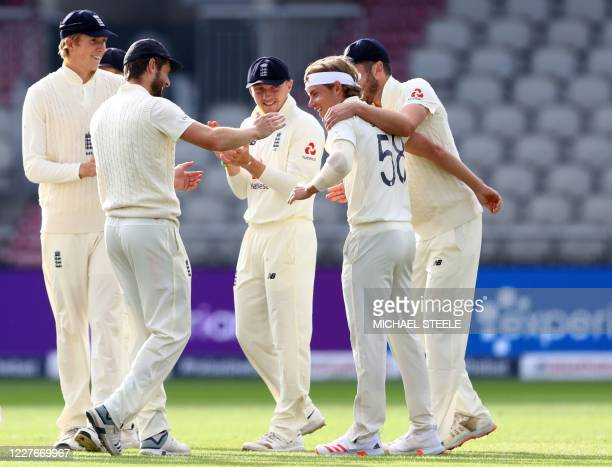 England's Sam Curran celebrates with teammates after taking the wicket of West Indies' John Campbell, given out after a review, during play on the...