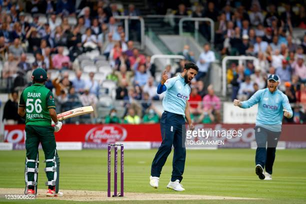 England's Saqib Mahmood celebrates with England's Ben Stokes after trapping Pakistan's Babar Azam LBW for 19 runs during the second one day...