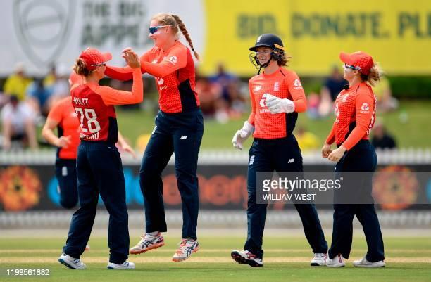 England's Sophie Ecclestone celebrates with teammates after dismissing Australia's batswoman Ashleigh Gardner during their women's T20 International...