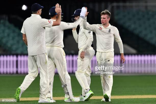 England's spin bowler Mason Crane celebrates his wicket of Cricket Australia XI's batsman Simon Milenko with teammates on the second day of a fourday...