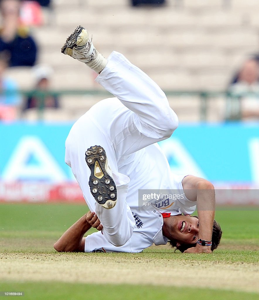 England's Steven Finn falls as he takes the wicket of Jahurul Isam of Bangladesh during the third day of the second Test match between England and Bangladesh at Old Trafford in Manchester, northwest England, on June 6 2010.