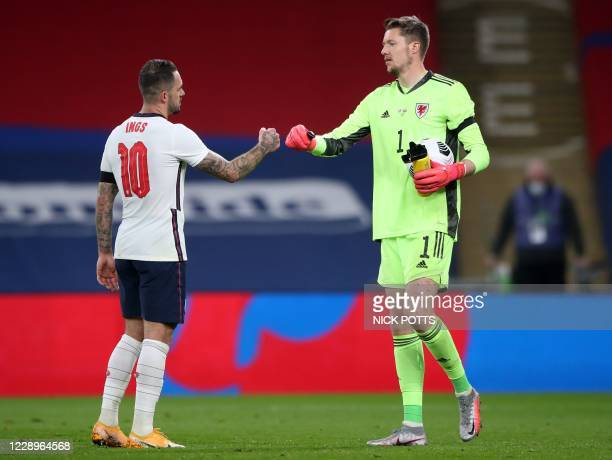 England's striker Danny Ings and Wales' goalkeeper Wayne Hennessey fist bump after the international friendly football match between England and...