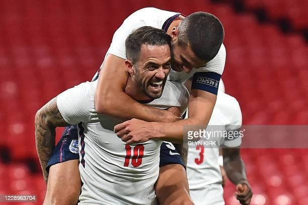 England's striker Danny Ings celebrates with England's defender Conor Coady after scoring their third goal with this overhead kick during the...