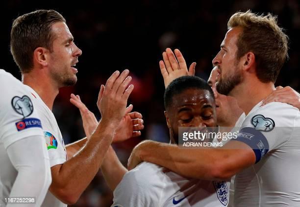 England's striker Harry Kane celebrates scoring his team's second goal with England's midfielder Jordan Henderson and England's midfielder Raheem...