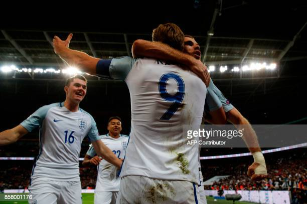 England's striker Harry Kane celebrates with teammates England's defender Michael Keane and England's midfielder Jordan Henderson after scoring the...