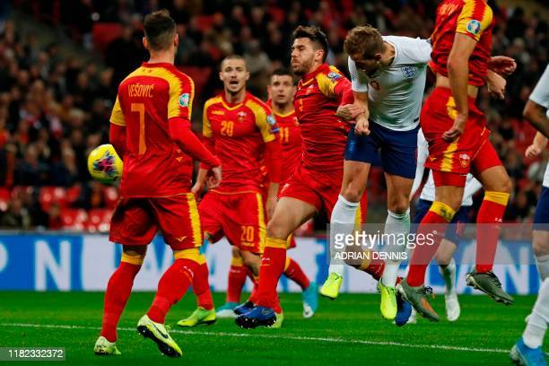 England's striker Harry Kane heads home their third goal during the UEFA Euro 2020 qualifying first round Group A football match between England and...