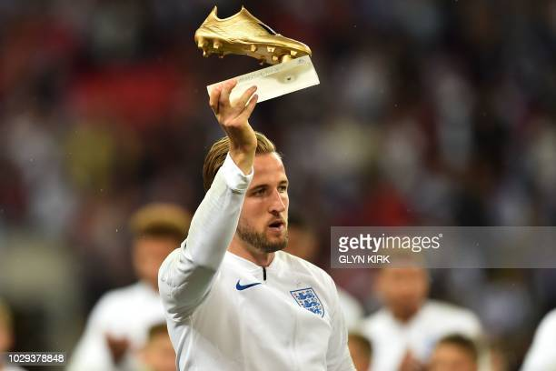 England's striker Harry Kane is presented with his Golden Boot award for being the top goalscorer at the 2018 World Cup in Russia ahead of the UEFA...
