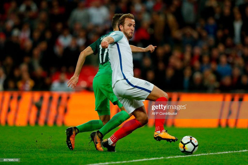 England's striker Harry Kane (R) scores the opening goal during the FIFA World Cup 2018 qualification football match between England and Slovenia at Wembley Stadium in London on October 5, 2017. / AFP PHOTO / Adrian DENNIS / NOT