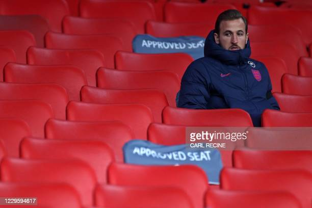England's striker Harry Kane takes his allocated seat in the stands for the international friendly football match between England and Republic of...