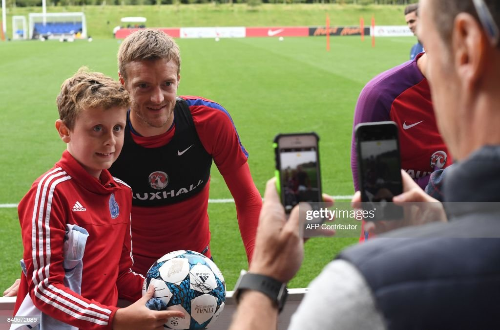 England's striker Jamie Vardy poses for a photograph with a young fan following a training session at St George's Park in Burton-on-Trent on August 29, 2017, as part of an England football team media day ahead of their 2018 FIFA World Cup qualifier matches against Malta on September 1 and Slovakia on September 4. / AFP PHOTO / Paul ELLIS / NOT