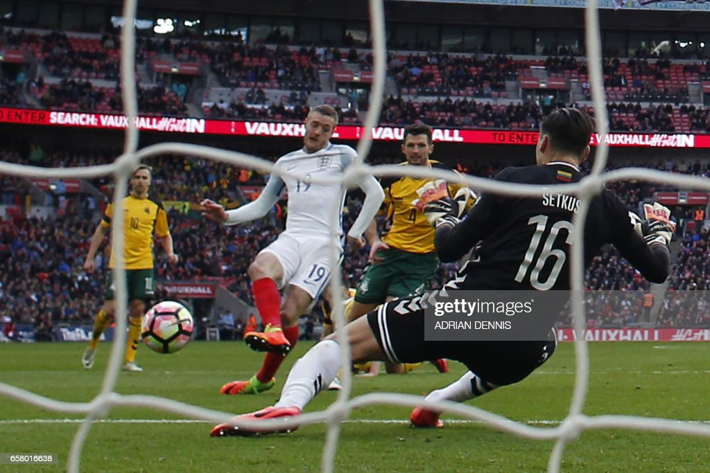 England's striker Jamie Vardy (centre left) shoots past Lithuania's goalkeeper Ernestas Setkus to score their second goal during the World Cup 2018 qualification football match between England and Lithuania at Wembley Stadium in London on March 26, 2017. England won the game 2-0. / AFP PHOTO / Adrian DENNIS / NOT