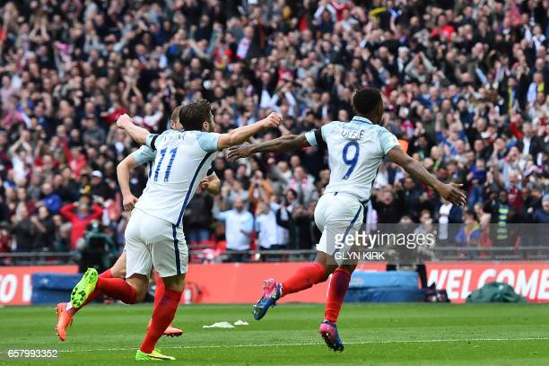 England's striker Jermain Defoe celebrates with teammates after scoring the opening goal of the World Cup 2018 qualification football match between...
