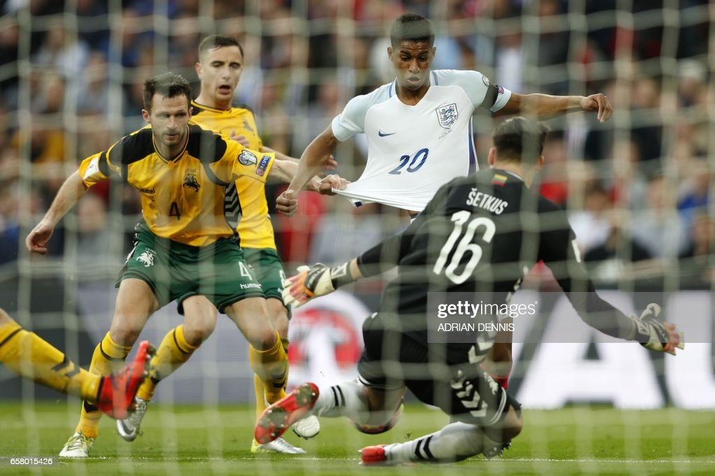 England's striker Marcus Rashford (2nd R) has his shirt pulled by Lithuania's defender Tadas Kijanskas as he runs in on goal during the World Cup 2018 qualification football match between England and Lithuania at Wembley Stadium in London on March 26, 2017. England won the game 2-0. / AFP PHOTO / Adrian DENNIS / NOT