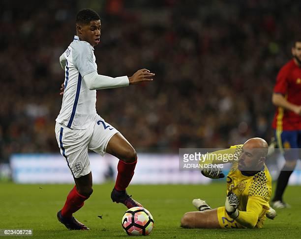 England's striker Marcus Rashford runs the ball around Spain's goalkeeper Pepe Reina but fails to score during the friendly international football...