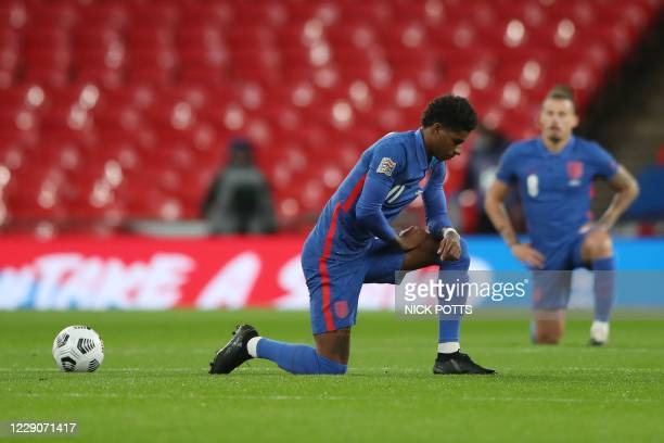 England's striker Marcus Rashford takes a knee to show solidarity with the Black Lives Matter campaign against racism before kick off of the UEFA...