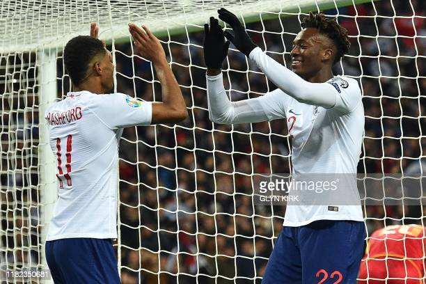 England's striker Tammy Abraham and England's striker Marcus Rashford celebrate their sixth goal an own goal scored by Montenegro's defender...