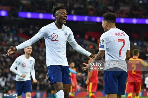 England's striker Tammy Abraham celebrates with England's midfielder Jadon Sancho after scoring their seventh goal during the UEFA Euro 2020...