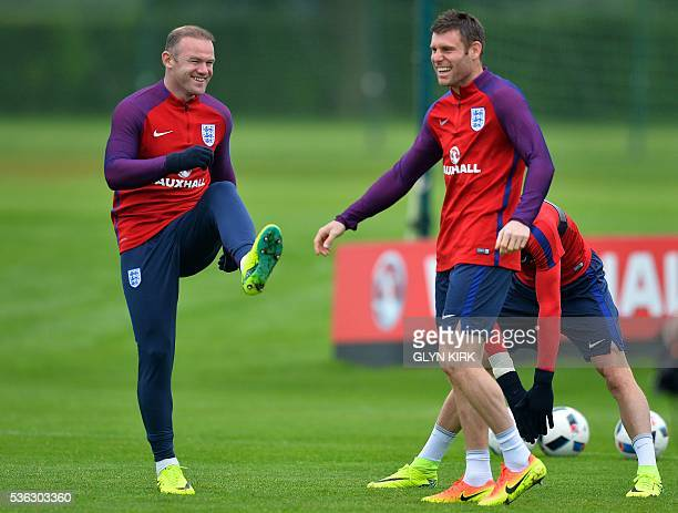 England's striker Wayne Rooney and England's midfielder James Milner react as they warm up during a team training session in Watford north of London...