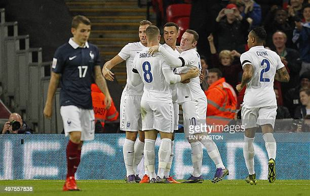 England's striker Wayne Rooney celebrates with team mates after scoring his team's second goal during the friendly football match between England and...