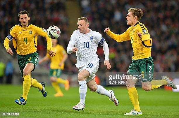 England's striker Wayne Rooney is challenged by Lithuania's Marius Zaliukas and Lithuania's Tadas Kijanskas during a Euro 2016 Group E qualifying...