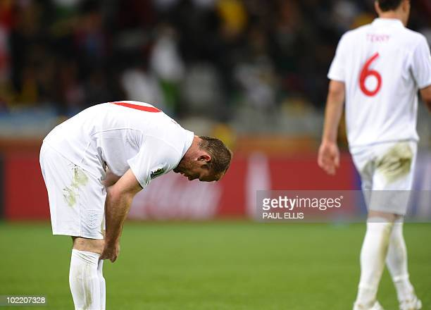 England's striker Wayne Rooney leans over after the Group C first round 2010 World Cup football match England versus Algeria as his teammate...