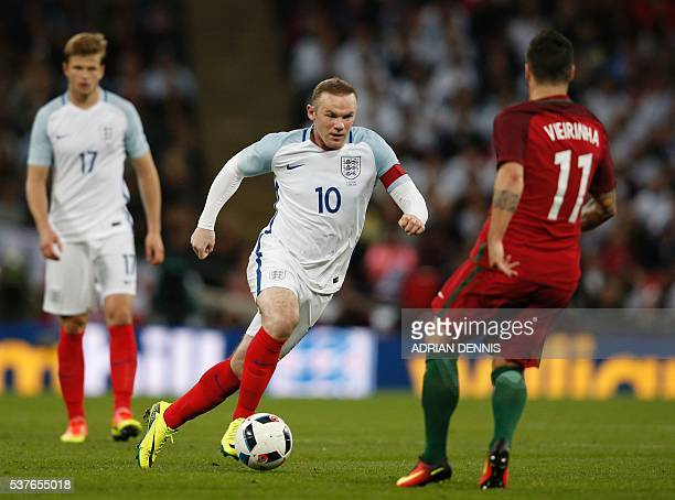 England's striker Wayne Rooney vies with Portugal's Vieirinha during the friendly football match between England and Portugal at Wembley stadium in...