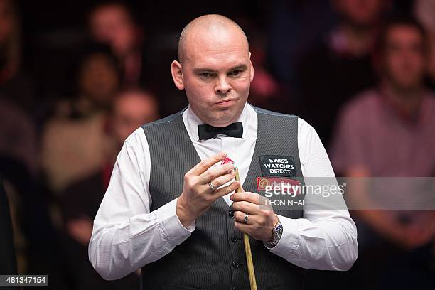 England's Stuart Bingham chalks his cue during his first round match against Hong Kong snooker player Marco Fu at the Masters snooker tournament at...