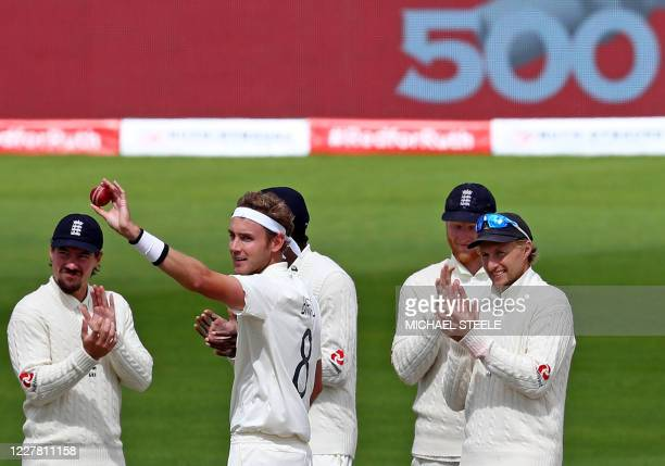 England's Stuart Broad holds the ball aloft as he celebrates taking the wicket of West Indies' Kraigg Brathwaite, his 500th Test wicket, on the final...