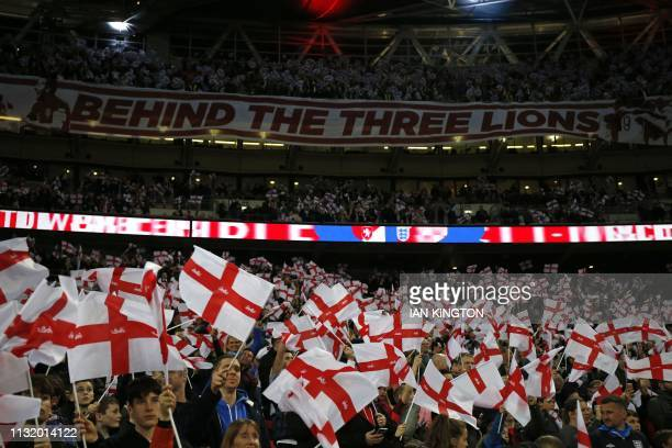 England's supporters wave flags during the playing of the national anthem ahead of the UEFA Euro 2020 Group A qualification football match between...