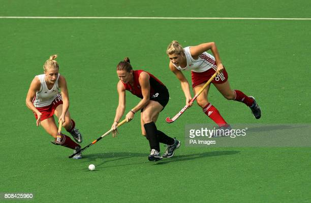 England's Susannah Gilbert and Georgie Twigg compete against Wales' Sarah Thomas for the ball in the hockey preliminary round match during Day Two of...