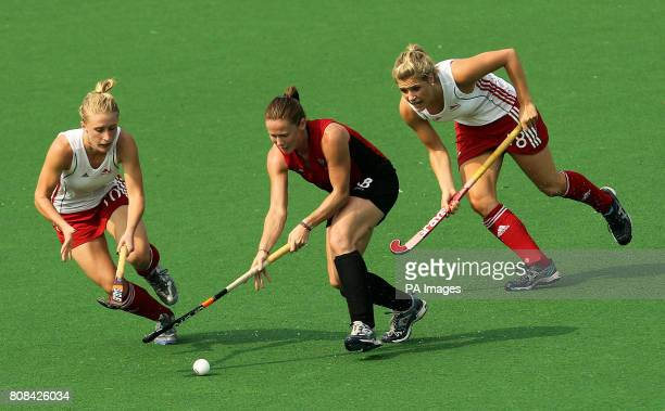 CROP* England's Susannah Gilbert and Georgie Twigg compete against Wales' Sarah Thomas for the ball in the hockey preliminary round match during Day...
