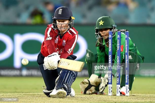 England's Tammy Beaumont plays a reverse sweep shot as Pakistan's wicketkeeper Sidra Nawaz looks on during the Twenty20 women's World Cup cricket...