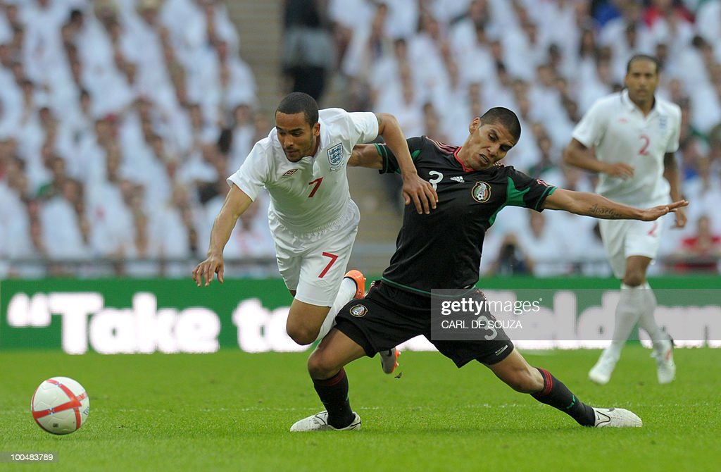 England's Theo Walcott (L) is challenged during their international friendly football match at Wembley Stadium in London on May 24, 2010 AFP PHOTO/Carl de Souza