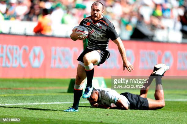 England's Tom Bowen breaks through a Fijian tackle during their match on the second day of the World Rugby Sevens Series at Cape Town Stadium in Cape...