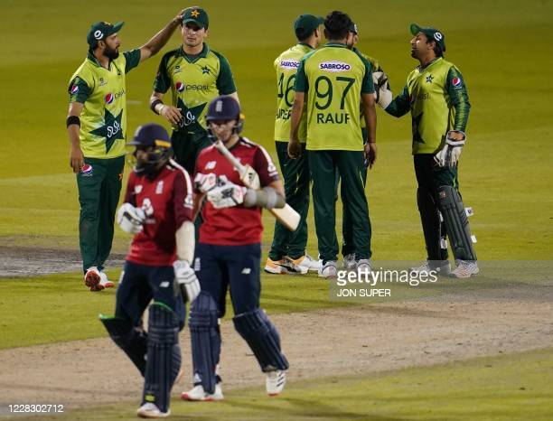 England's Tom Curran and England's Adil Rashid leave the field as Pakistan players celebrate winning by five runs after the international Twenty20...