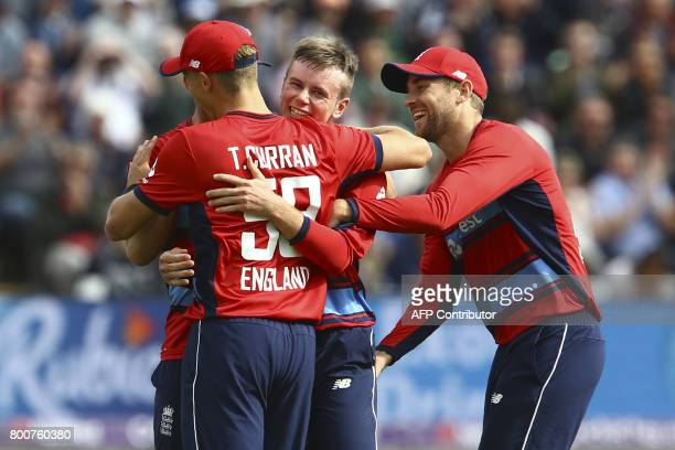 England's Tom Curran celebrates with team mates after England take the wicket of South Africa's AB de Villiers during the third Twenty20...