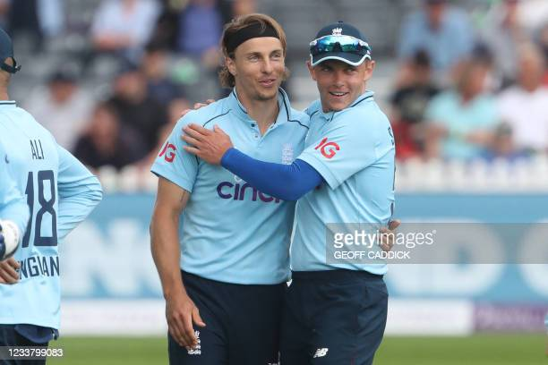England's Tom Curran is congratulated by his brother, England's Sam Curran after taking the wicket of Sri Lanka's Oshada Fernando during the third...