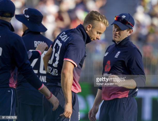 England's Tom Curran speaks with captain Eoin Morgan after taking a wicket during the fifth oneday international cricket match between England and...