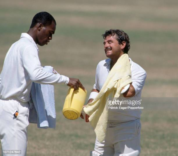 England's twelfth man Chris Lewis pours a drink for England batsman Allan Lamb during his innings of 132 runs in the 1st Test match between West...