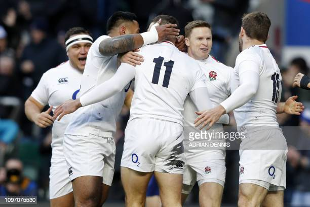 England's wing Jonny May celebrates with teammates after scoring an early try during the Six Nations international rugby union match between England...