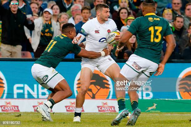 England's wing Jonny May is tackled by South Africa's centre Aphiwe Dyantyi as South Africa's wing Lukhanyo Am looks on during the second test match...