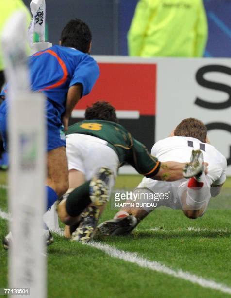 England's winger Mark Cueto scores a try tackled by South Africa's flanker Schalk Burger and canceled by Ireland's referee Alain Rolland during the...