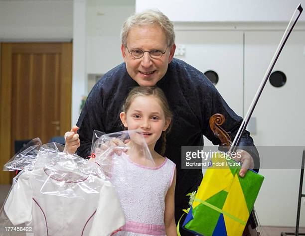 English 8yearold violin prodigy Alma Deutscher foreground and violonist Shlomo Mintz pose after performing as part of the CransMontana Classics...
