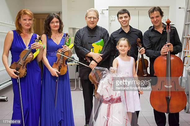 English 8yearold violin prodigy Alma Deutscher foreground violonist Shlomo Mintz and members of the New Russian Quartet violonists Elena Kharitonova...