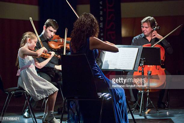 English 8yearold violin prodigy Alma Deutscher performs a piece of her own composition alongside from left violonists Michael Rudoy and Julia Igonina...