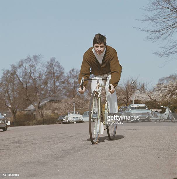 English actor Alan Bates who appears in the film 'Far From the Madding Crowd' pictured cycling on a road in London in 1967