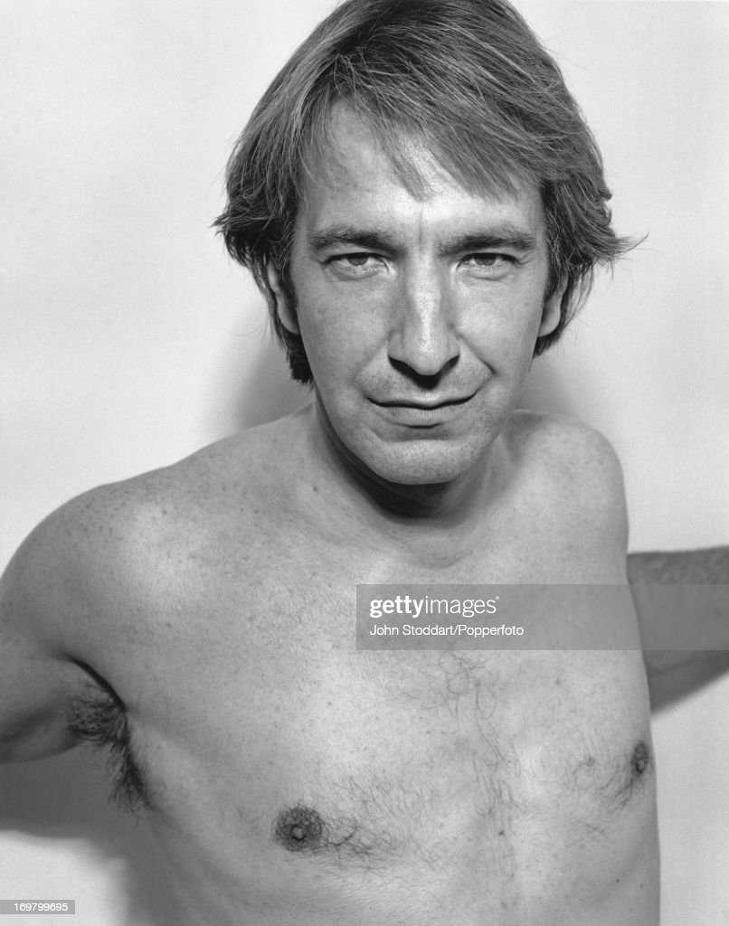 English actor Alan Rickman poses bare-chested, 1991.