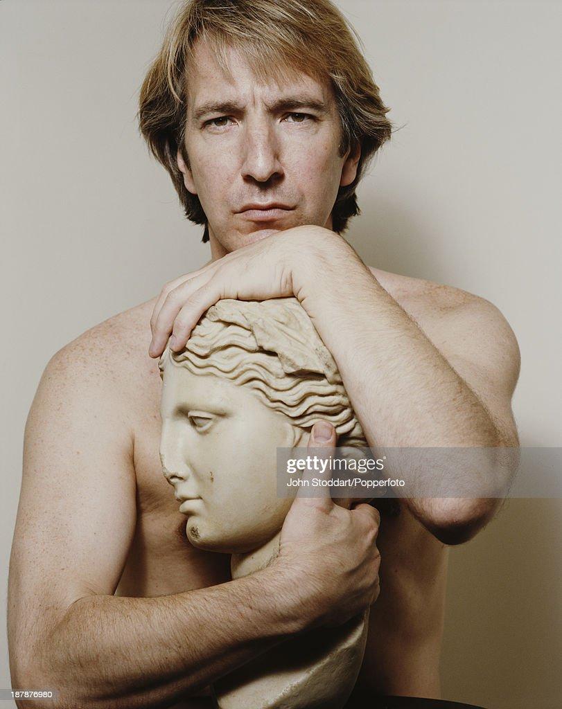 English actor Alan Rickman poses with a bust, 1991.