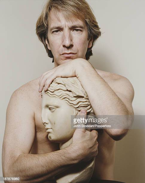 English actor Alan Rickman poses with a bust 1991