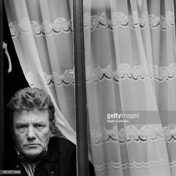 English actor Albert Finney posing behind a window Romney Street Salford circa 1985